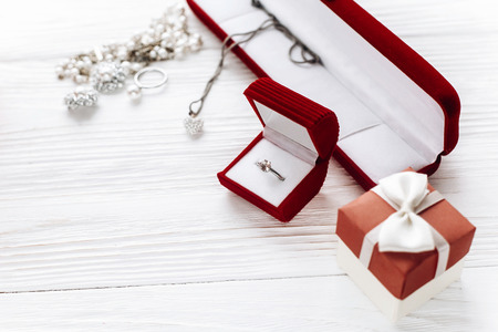 stylish diamond ring in red present box and luxury jewelry accessories on white rustic wooden background. happy valentine day card concept. greeting flat lay with space for text.