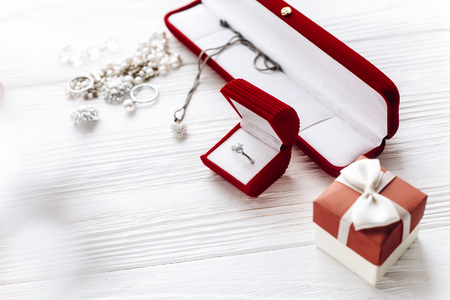 valentine day concept. stylish diamond ring in red present box and luxury jewelry accessories on white rustic wooden background. greeting flat lay with space for text