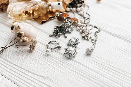 luxury expensive jewelry rings earrings and perfume on white rustic wooden table with space for text. flat lay. fashion blogger. modern woman set of  accessories and rich essentials 스톡 콘텐츠