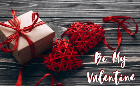 be my valentine text sign. stylish present and two red hearts with ribbon on rustic black wooden background. happy valentine day concept. greeting card flat lay with space for text.