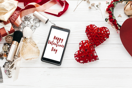 admire: happy valentines day text sign on smart phone  screen and luxury jewelry perfume makeup and hearts flat lay on white background, space for text. modern woman set Stock Photo