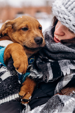 stylish hipster girl hugging cute puppy in snowy cold winter park. moments of true happiness. adoption concept. save animals