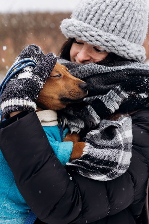 stylish hipster girl hugging and caressing cute puppy in snowy cold winter park. moments of true happiness. adoption concept. save animals