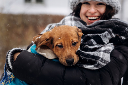 stylish hipster woman hugging and smiling cute puppy in snowy cold winter park. moments of true happiness. adoption concept. save animals
