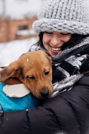 stylish hipster woman hugging and caressing cute puppy in snowy cold winter park. moments of true happiness. adoption concept. save animals