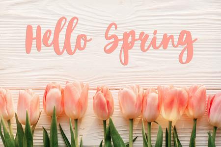 hallo lente tekst teken, mooie roze tulpen op witte rustieke houten achtergrond plat lag. bloemen in zacht ochtendzonlicht met ruimte voor tekst. wenskaart concept