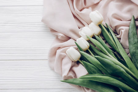 stylish white tulips on beige soft fabric and rustic wooden table background top view. hello spring flat lay. soft light, tenderness atmospheric moment. space for text. modern image Stock Photo