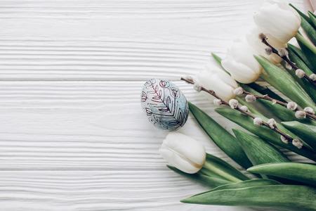 Carte de voeux joyeux Pâques. oeuf de Pâques élégant et bourgeons de saule et tulipes blanches sur fond plat en bois rustique poser. concept avec espace pour le texte, vue de dessus. Lumière douce Banque d'images - 73145476