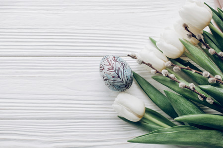 happy easter greeting card. stylish easter egg and willow buds and white tulips on rustic wooden background flat lay. concept with space for text, top view. soft light Stok Fotoğraf