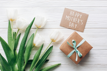 happy mothers day text sign on stylish craft present box and greeting card and tulips on white wooden rustic background. flat lay with flowers empty paper with space for text. holiday gift