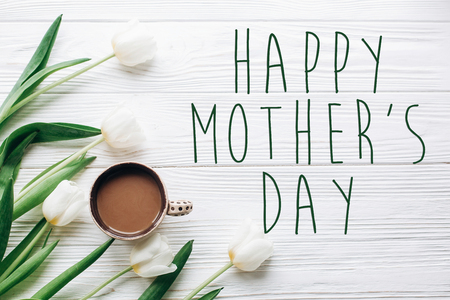 happy mothers day text sign on tulips and coffee on white wooden rustic background. stylish flat lay with flowers and drink with space for text. greeting card.  happy day concept