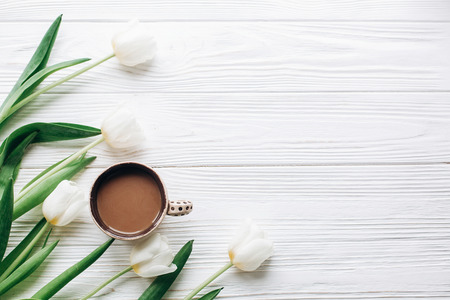 tulips and coffee on white wooden rustic background. stylish flat lay with flowers and drink with space for text. greeting card. hello spring. happy day concept