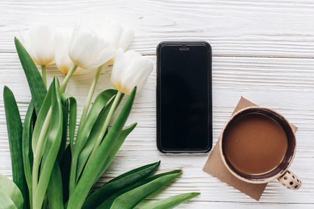 phone and tulips and morning coffee on white wooden rustic background. flat lay with flowers and gadget with empty screen with space for text. hello spring concept. good morning