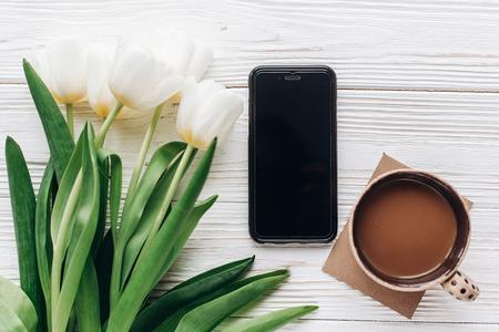 Téléphone et tulipes et café du matin sur fond rustique en bois blanc. appartement poser avec des fleurs et gadget avec un écran vide avec un espace pour le texte. Bonjour concept de printemps. Bonjour Banque d'images - 73145431