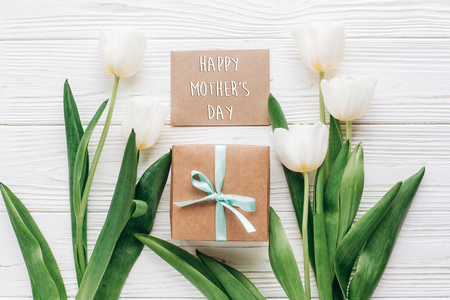 happy mothers day text sign on greeting card with stylish present box and tulips on white wooden rustic background. flat lay mock up with flowers and empty paper with space for text.
