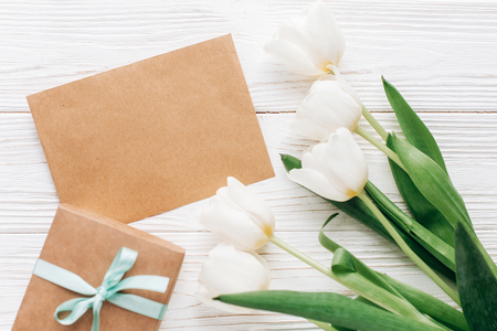 stylish craft present with greeting card and tulips on white wooden rustic background. flat lay with flowers and gift with space for text. happy mothers womens day concept. greeting card