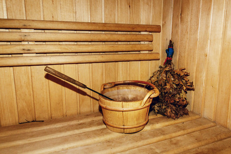 Russian wooden sauna room, lumber rustic bench in bath house, wooden bucket with water and birch leaf broom, healthy leisure relaxing hobby concept