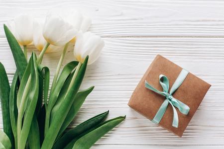 세련 된 공예 선물 상자와 흰색 나무 소박한 배경에 튤립. 평면 누워 꽃과 공간 텍스트와 선물. 안녕 봄. 행복 한 하루 개념입니다.