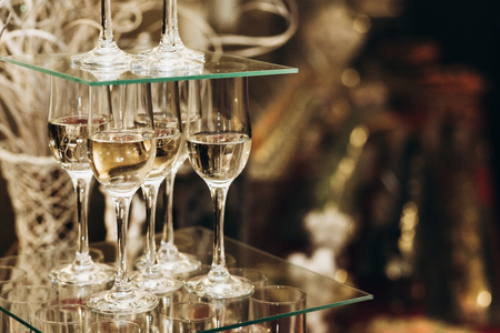 Elegant champagne glasses catering, tiered alcohol drinks on glass table, business dinner party reception in luxury restaurant close-up, catering concept