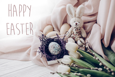 happy easter text greeting card sign on stylish easter eggs with chick ornaments in nest and bunny rabbit and tulips and willow buds on rustic white wooden background. space for text, soft light