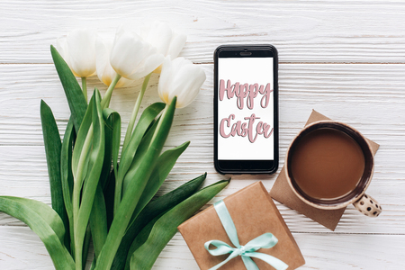 happy easter text greeting card sign on empty phone and tulips and coffee gift on white wooden rustic background. flat lay with flowers and gadget with space for text.