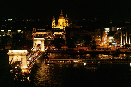 amazing night view of  bridge and river and city lights and boat in Budapest city,  travel concept, space for text