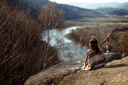 美しいネイティブ インド アメリカ人女性シャーマン岩の上に座って、森と川を見て