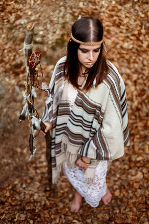 beautiful native indian american woman holding pikestaff with dream catcher on background of forest