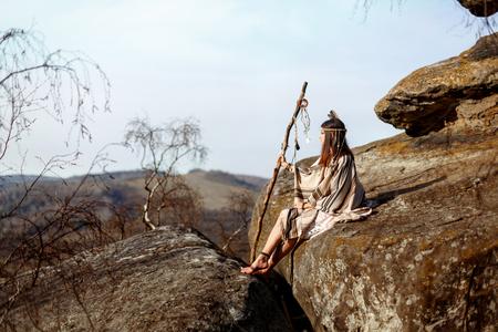 Hermosa mujer india americana indio sosteniendo pikestaff sentado en las rocas y mirando a los bosques y el río Foto de archivo - 75146938