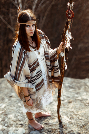first nations: beautiful native indian american woman with warrior shaman make up looking and holding rod