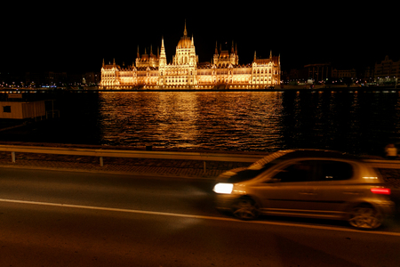 amazing night view of oparliament building and river and city lights at car crossing road in Budapest city, travel concept, space for text