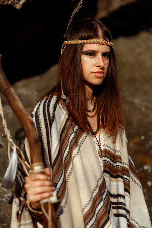 first nations: beautiful native indian american woman with warrior shaman make up on background of woods