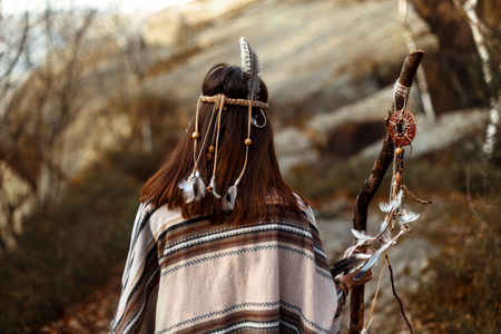 beautiful native indian american woman on background of woods and rocks