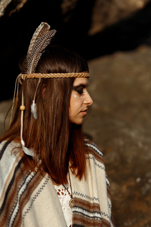 beautiful native indian american woman with warrior shaman make up on background of woods