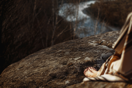 legs native indian american woman with warrior shaman make up sitting on rocks on background of woods and river