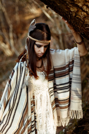 first nations: beautiful native indian american woman with warrior shaman make up walking under trees