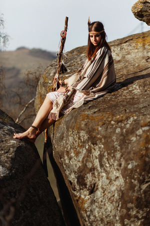 first nations: beautiful native indian american woman holding pikestaff sitting on rocks and looking at woods and river