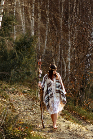 beautiful native indian american woman with pikestaff walking on background of woods