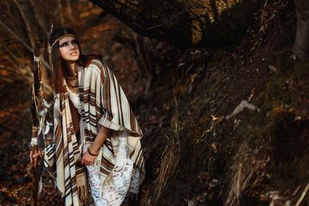 beautiful native indian american woman with warrior shaman make up walking under trees