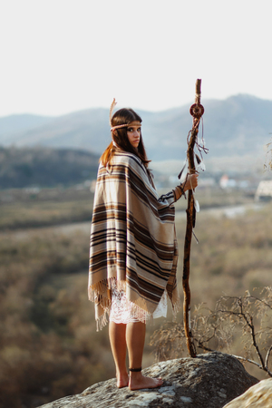 beautiful native indian american woman with warrior shaman make up standing on rocks on background of woods and river