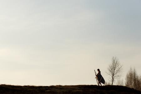 Silhouette der einheimischen indischen amerikanischen Frau zu Fuß auf Hügel zwischen Bäumen im Sonnenuntergang Abend Berge