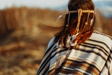 back of native indian american woman walking in mountains in evening, hair with feathers