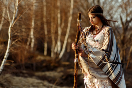 native indian american woman shaman on hill  in sunset evening mountains