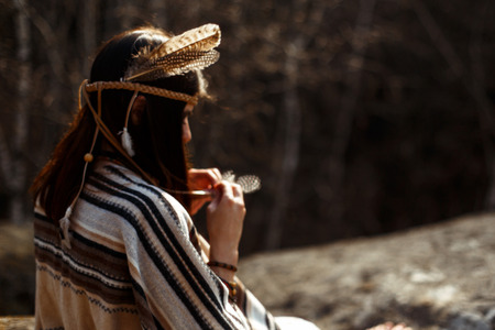 first nations: beautiful native indian american woman shaman  sitting on rocks and looking at woods and river