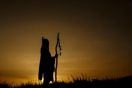 silueta del chamán nativo americano con pikestaff en el fondo de la hermosa puesta de sol en las montañas Foto de archivo