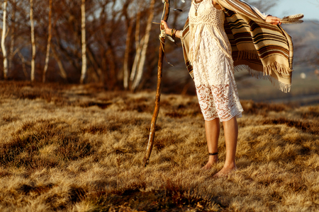 vrouw benen in inheemse Indiase Amerikaanse boho jurk wandelen in winderige zonnige avond bergen, veren te houden
