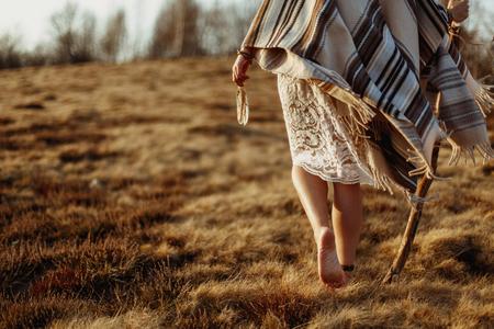 Piernas de la mujer en el vestido boho americano indio nativo caminando en las montañas soleadas ventosas de la tarde, sosteniendo plumas Foto de archivo