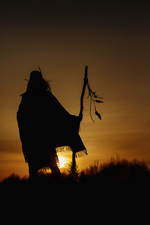 silhouette of native american shaman with pikestaff on background of sunset beutiful in mountains Standard-Bild