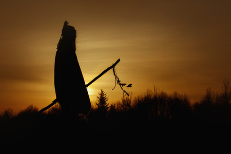 silhouette of native american shaman with pikestaff on background of sunset beutiful in mountains 版權商用圖片