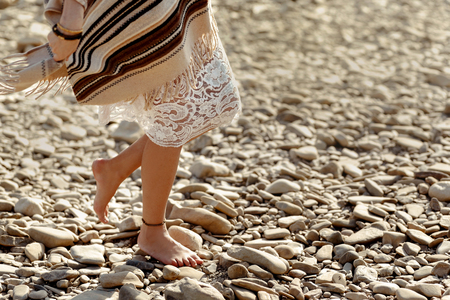 beautiful woman traveler walking barefoot  at river beach, legs close up, boho travel  concept, space for text